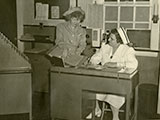Ward clerk consulting charge nurse at Grasslands Hospital, ca. 1950 (P-552).